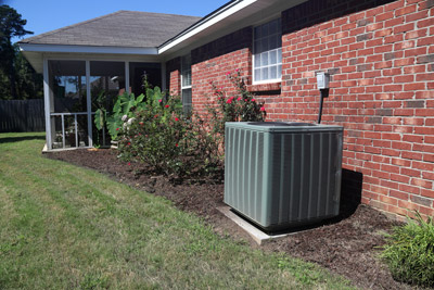 Air conditioner unit outside of brick home. Multnomah Heating will repair your air conditioner capacitor in the Portland, OR area.